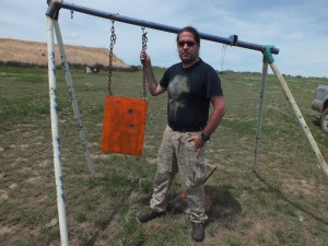 The author standing next to the 1,000 yard target. You can see each hit from the 3-shot group.